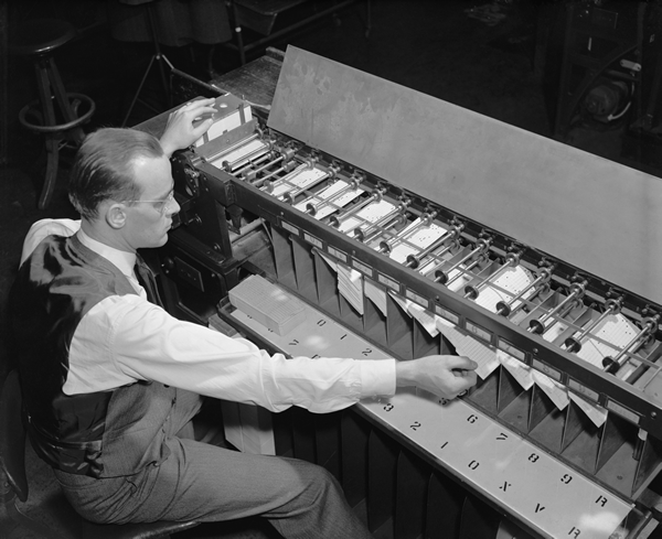 Black and white photo of man sitting at machine